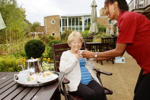 Patient being served aft tea on patio