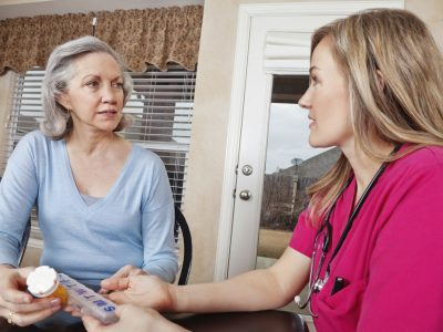 Nurse advising patient at home