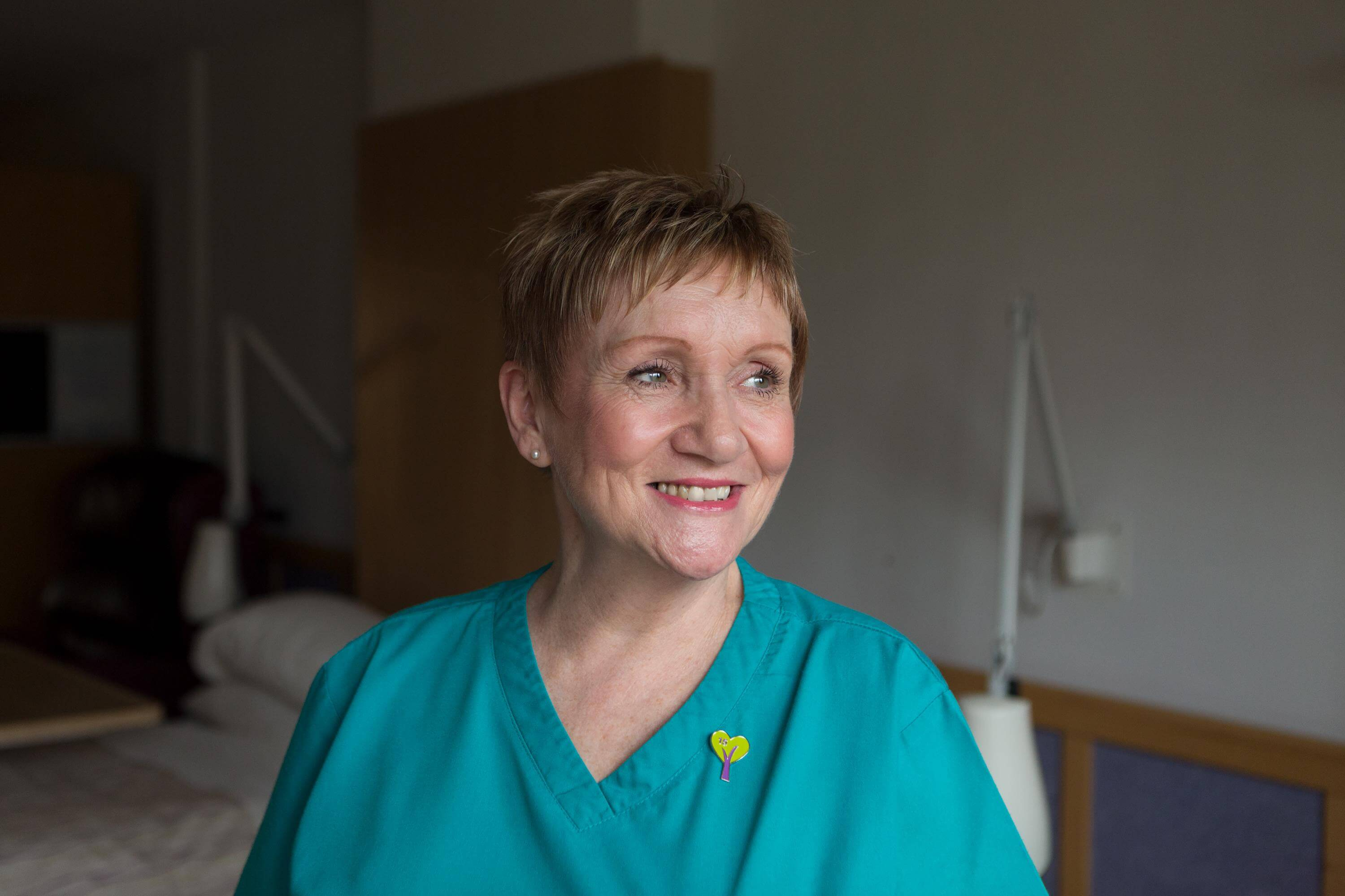 Smiling healthcare assistant in turquoise uniform