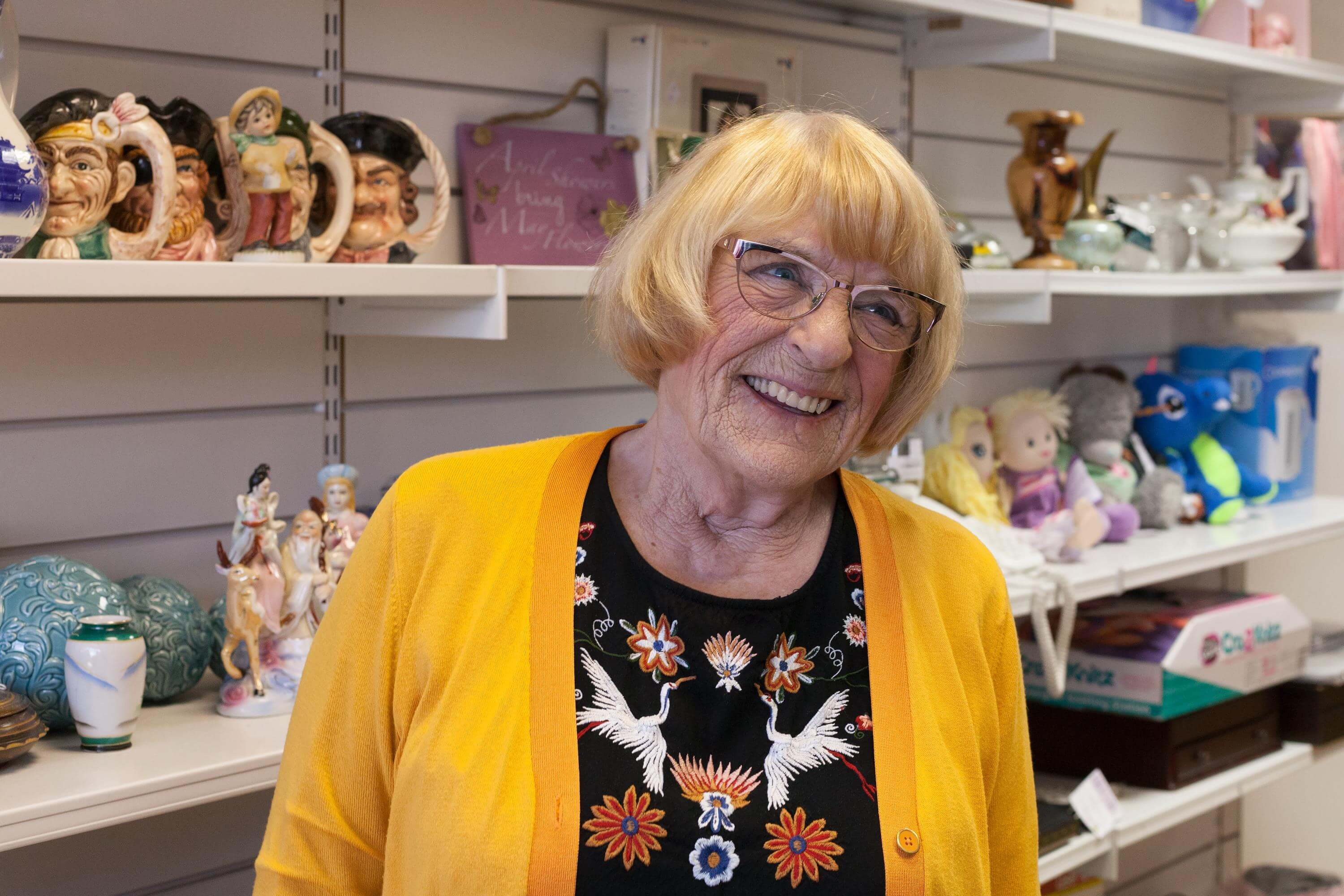 Woman smiling in front of shop shelves filled with bric-a-brac