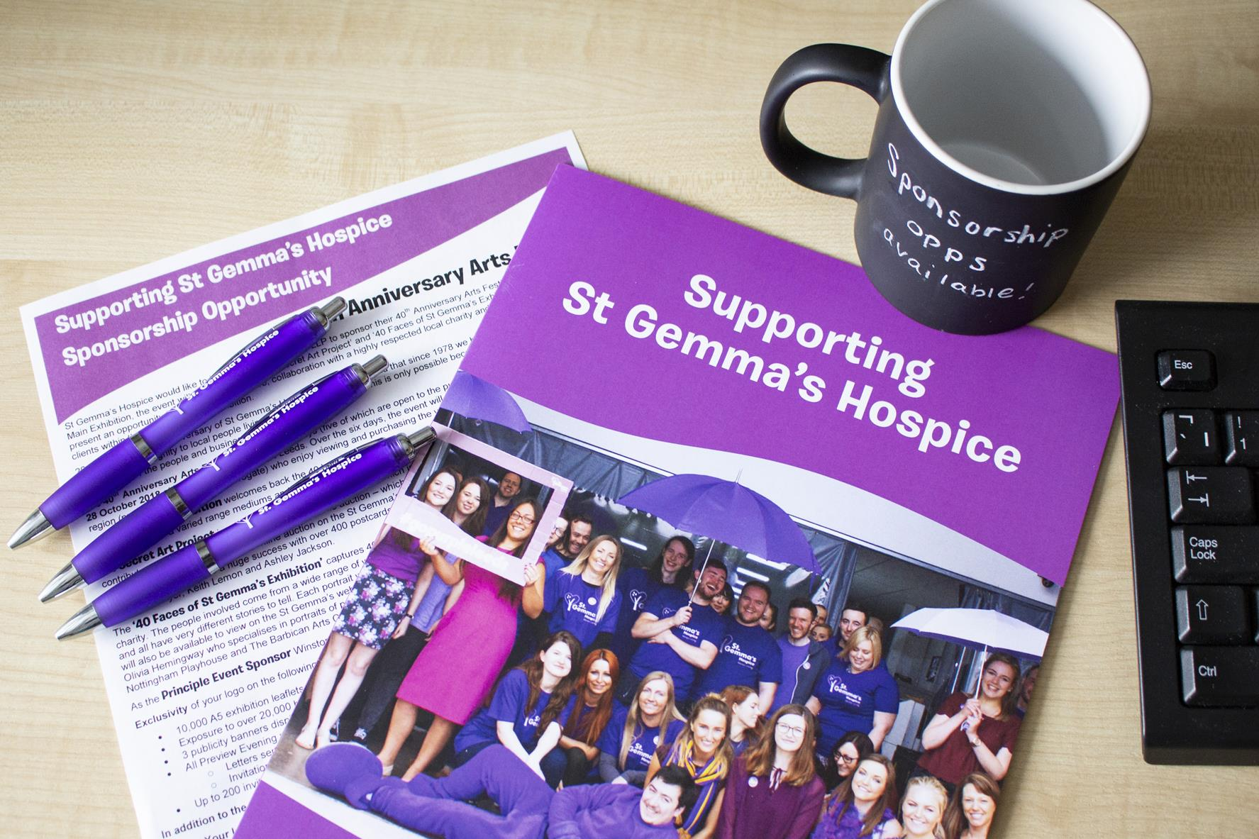 A copy of the 'Supporting St Gemma's Hospice' pack on a table next to a black mug that says 'Sponsorship Opportunities'.