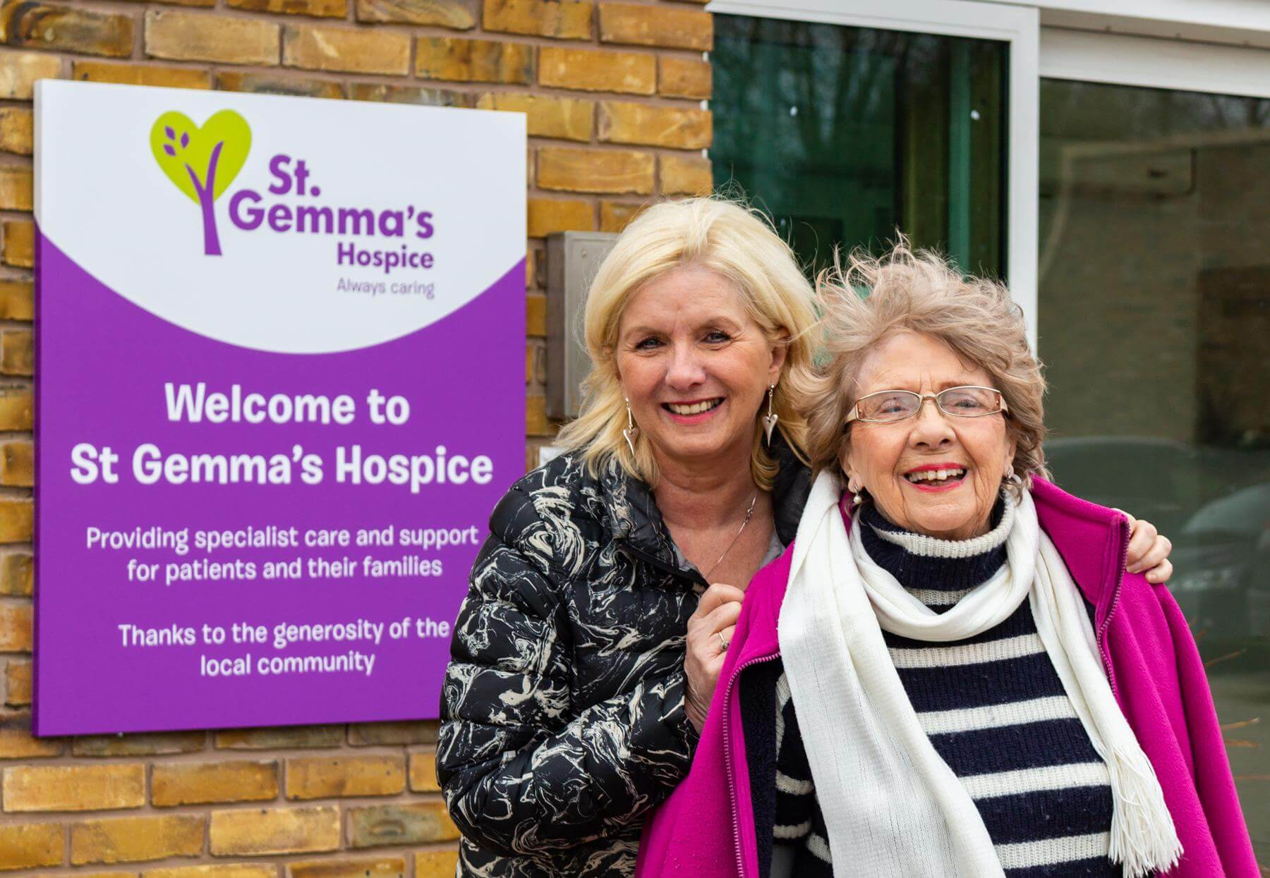 Women smiling next to St Gemma's Hospice sign