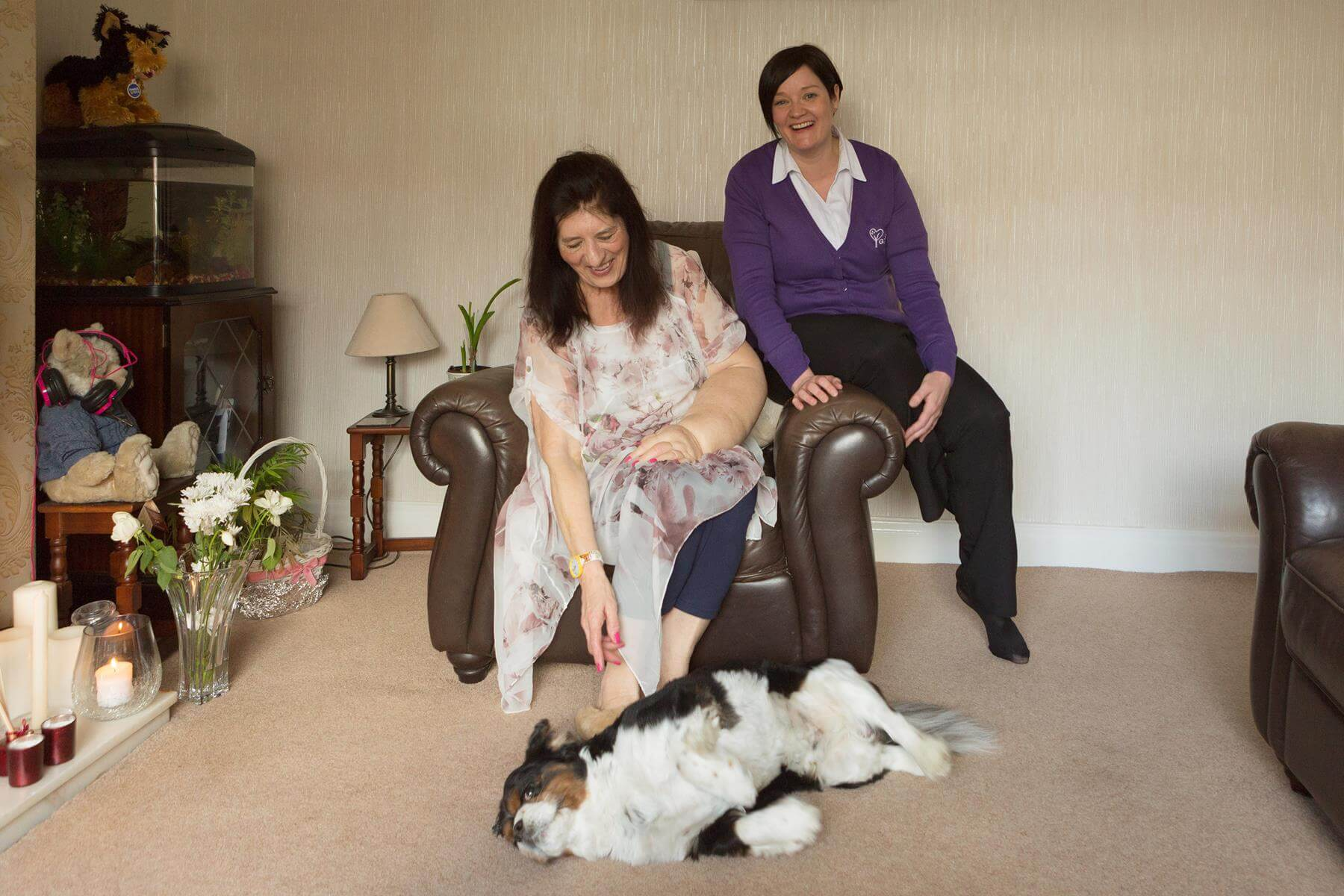 Community Nurse in a patient's living room with patient and their dog