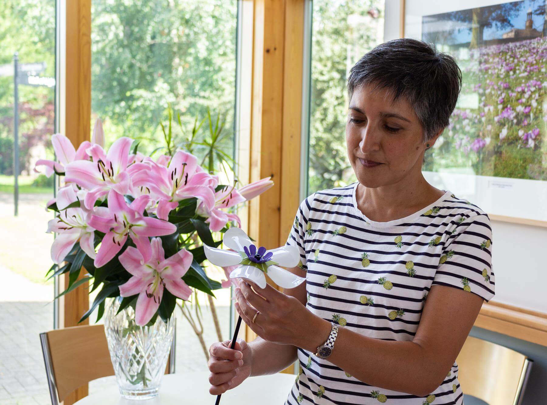 Women holding a white iron flower with pink flowers in the background