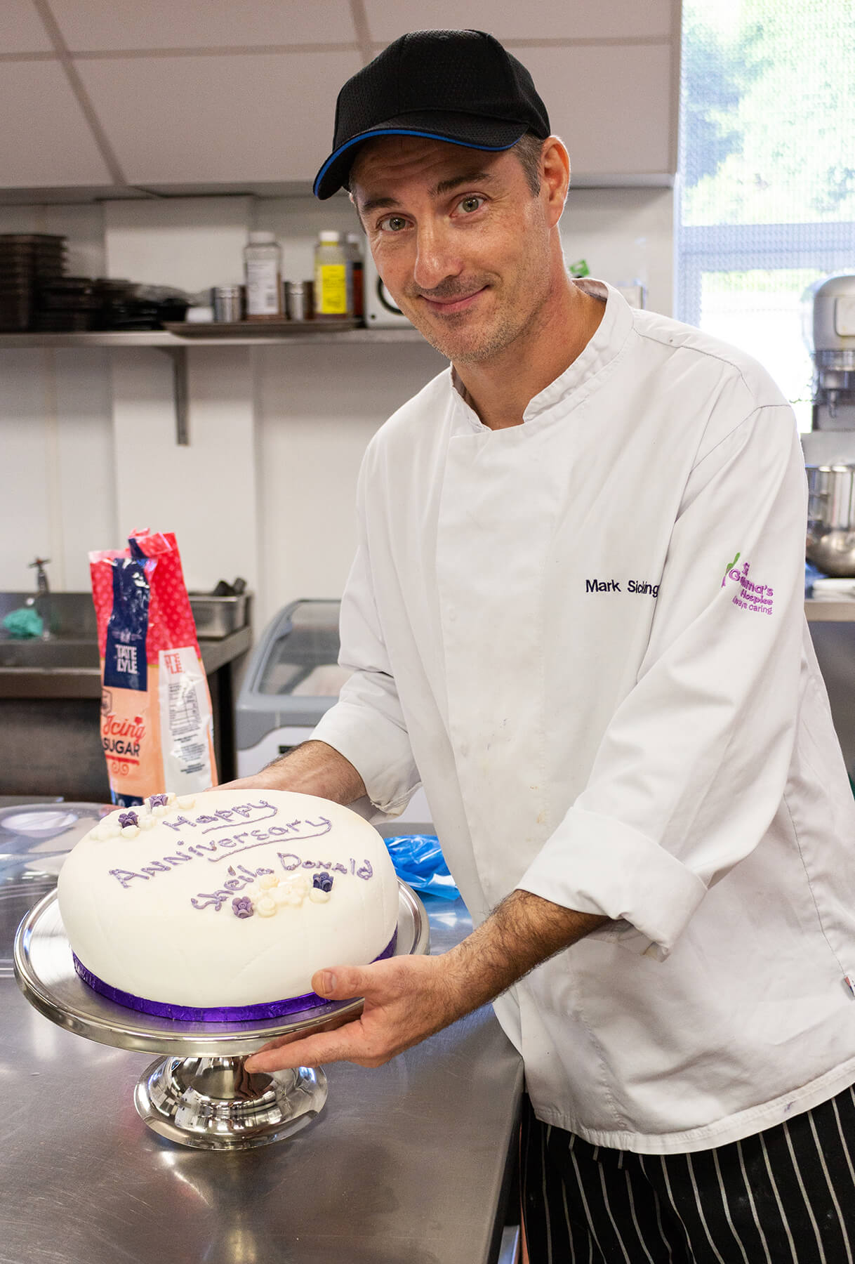 Chef holding cake with 'Happy Anniversary' iced on it.