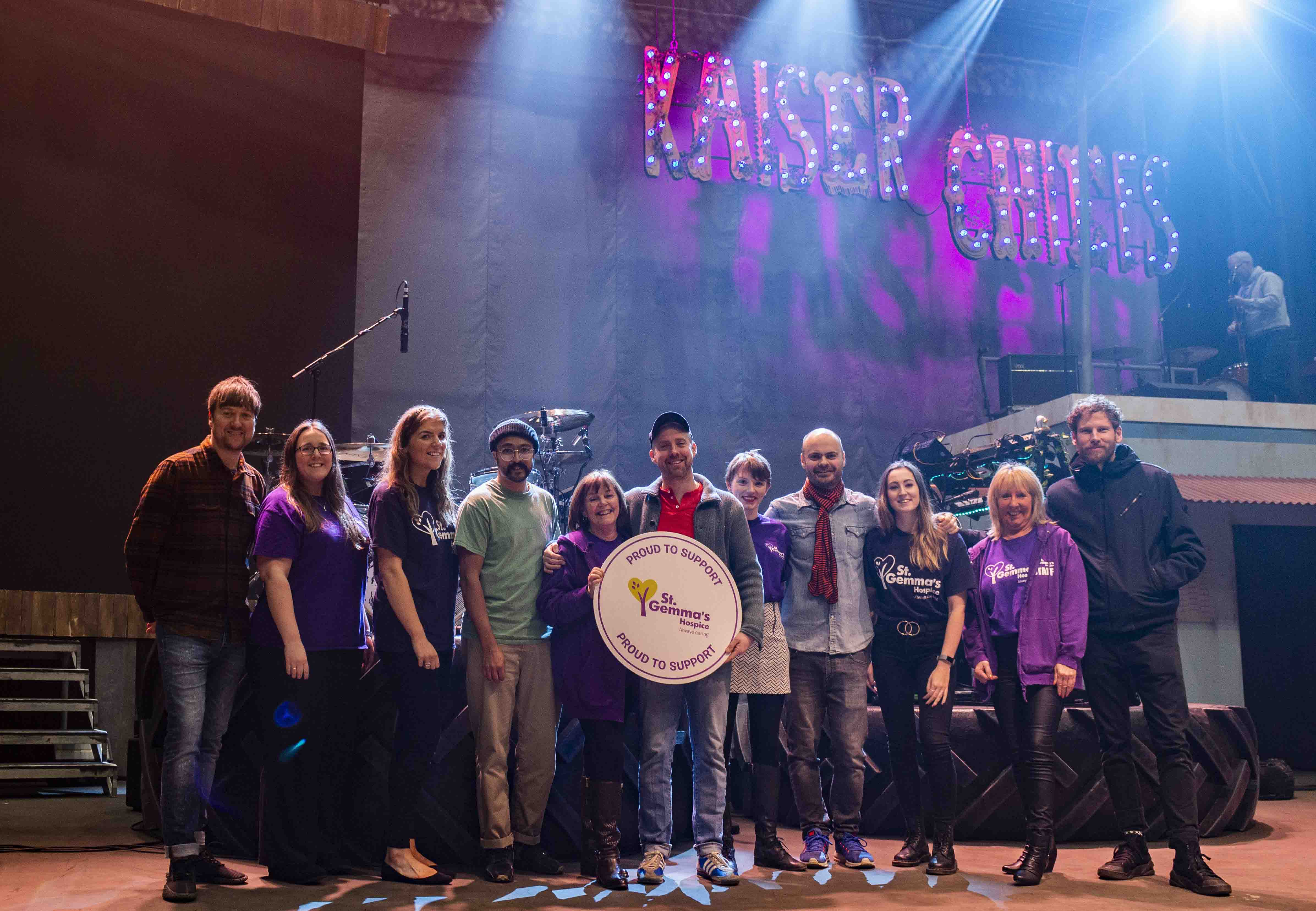 Kaiser Chiefs, with St Gemma's staff, holding 'Proud to Support' sign