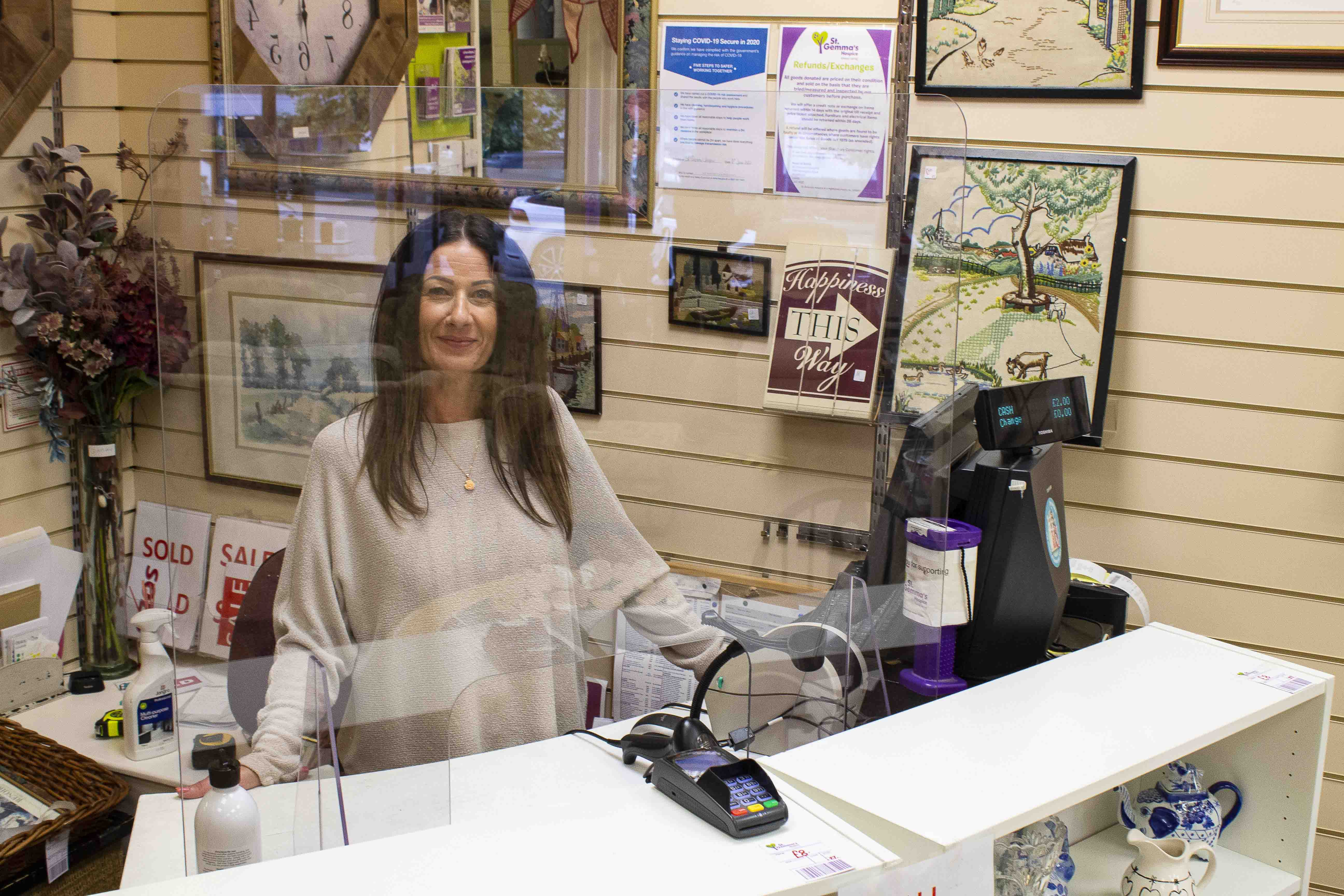 Smiling shop manager behind perspex screen at till
