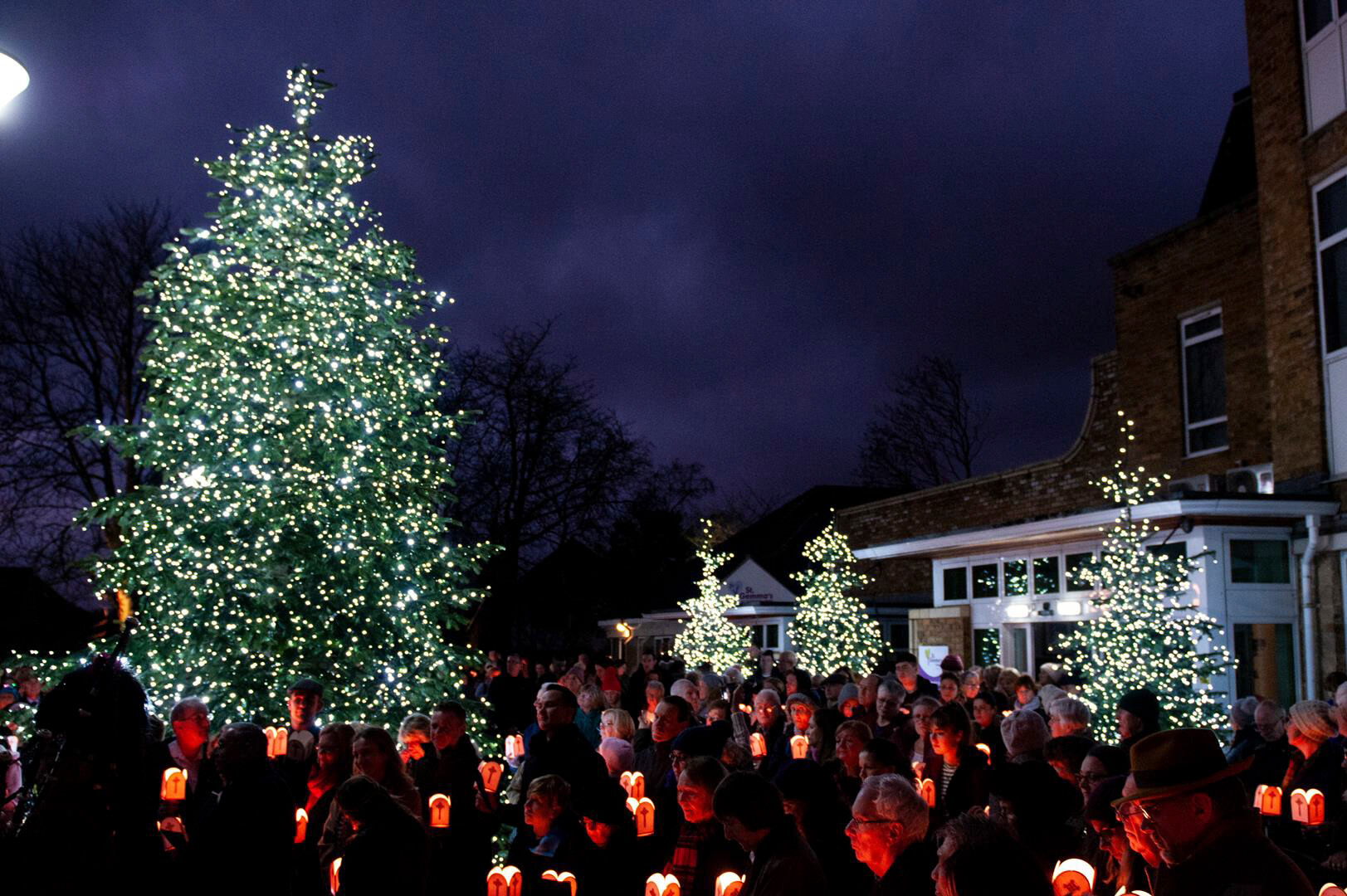 People gathered with lanterns; the sky is dark and bright lights are shining on Christmas trees
