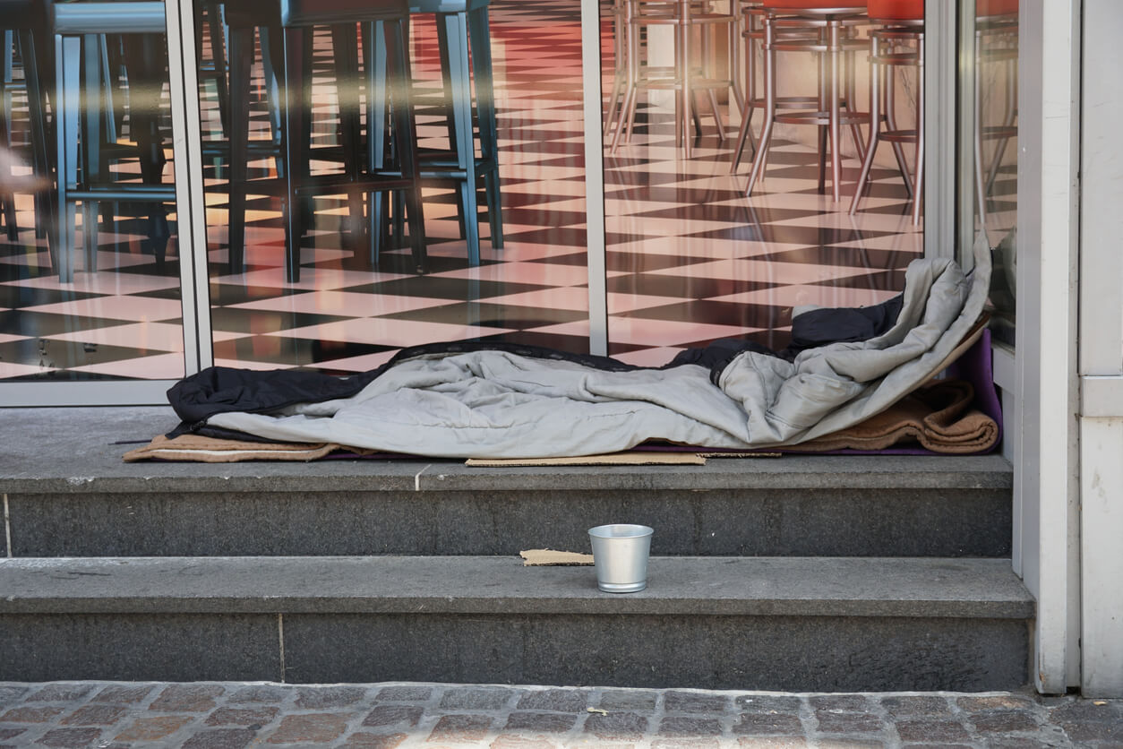 Sleeping bag of a homeless person spread on the stairs in front of a modern posh lounge or restaurant. There is a small metal cup near the berth asking for alms and charity.