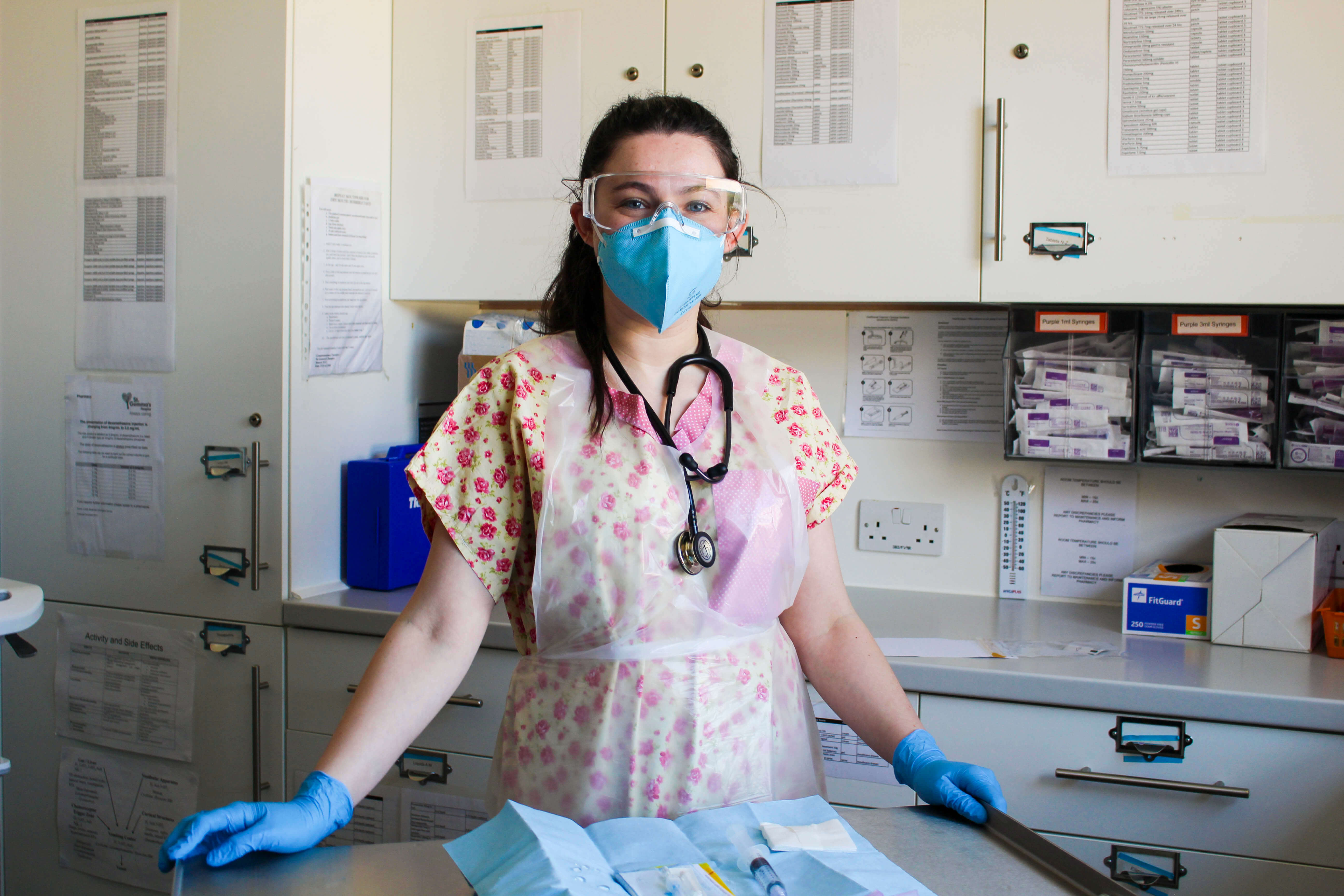 Healthcare worker wearing personal protective equipment of goggles, face mask, plastic apron and gloves.