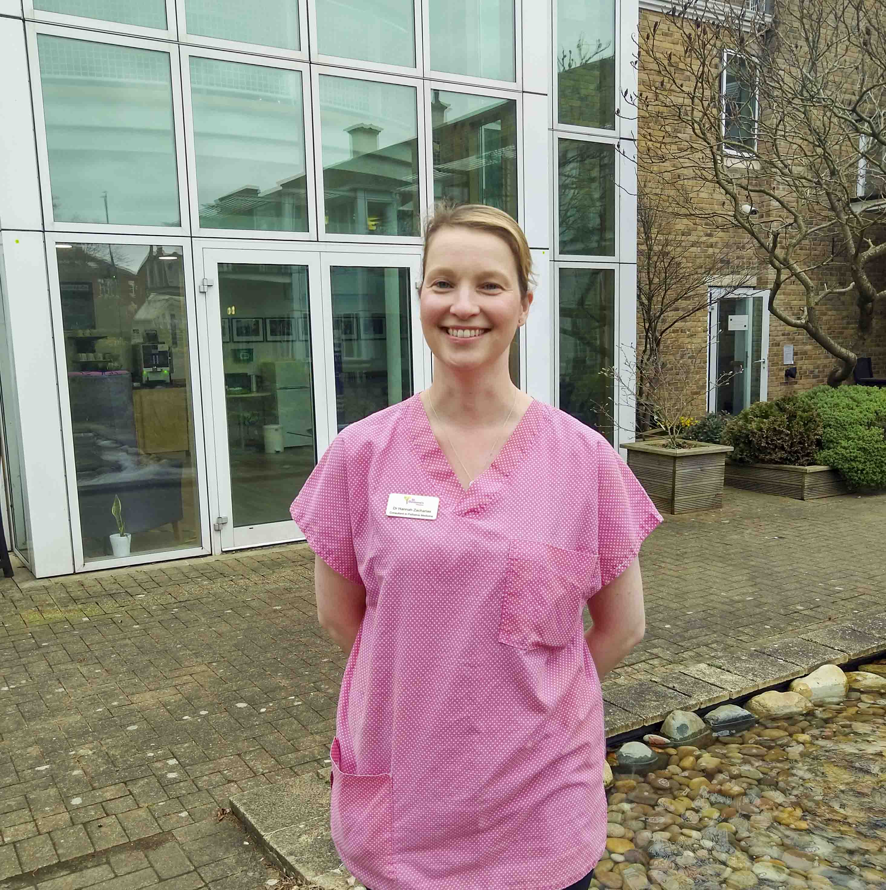 Doctor wearing a pink scrub top is standing in the hospice gardens and smiling
