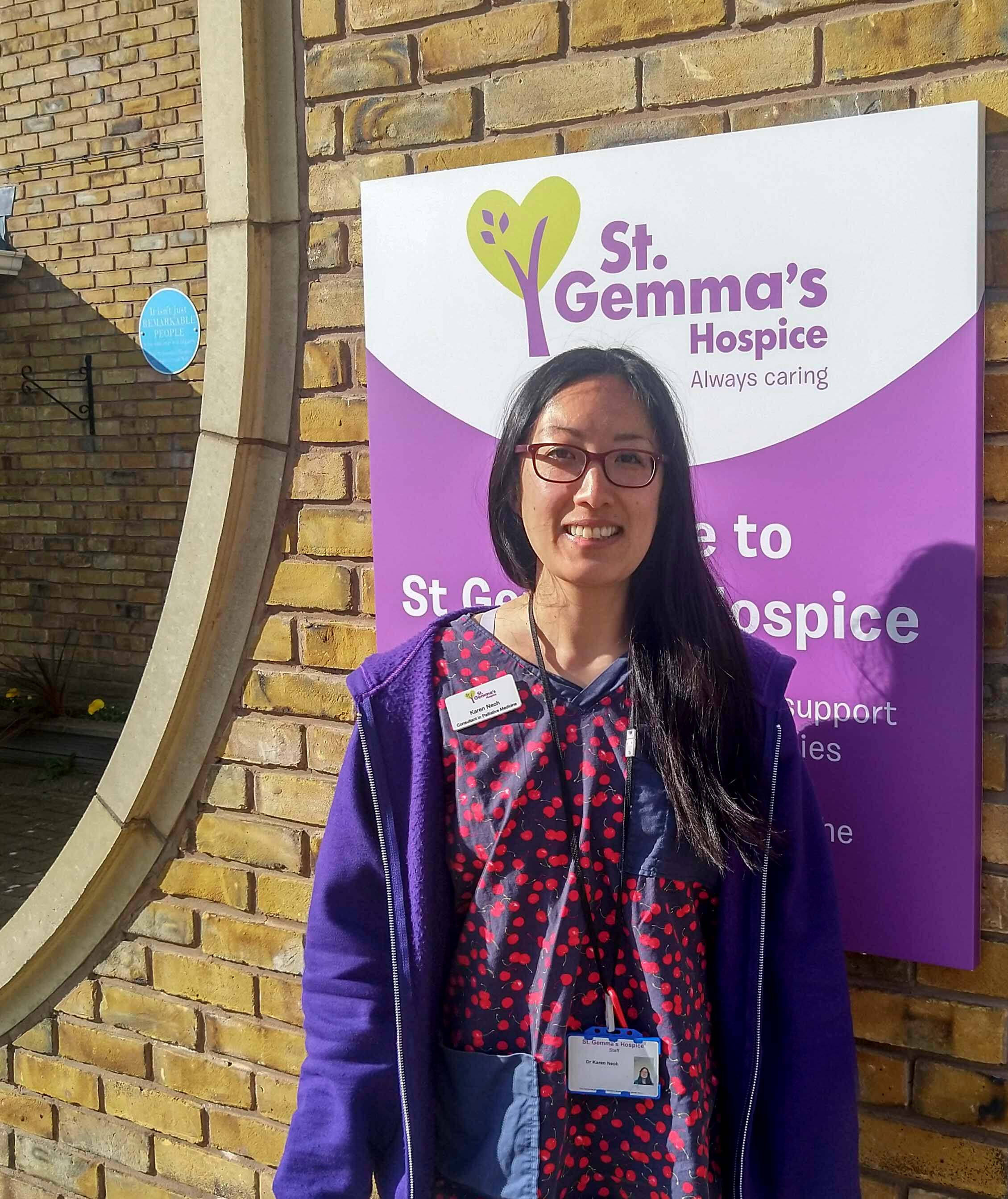 A doctor is standing outside the hospice with a St Gemma's sign behind her. She is wearing a navy and red scrub top.